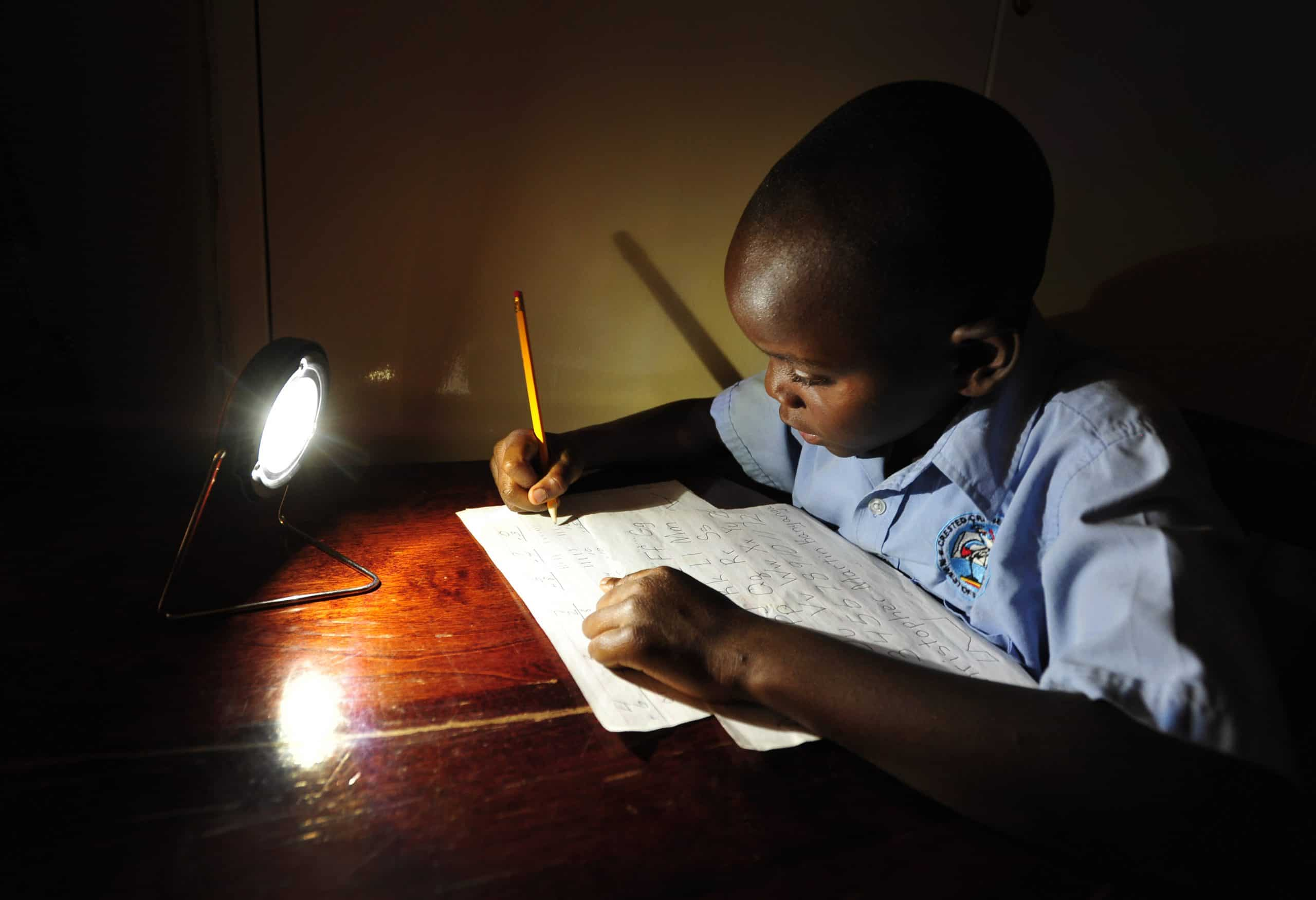 A boy writing by lamplight