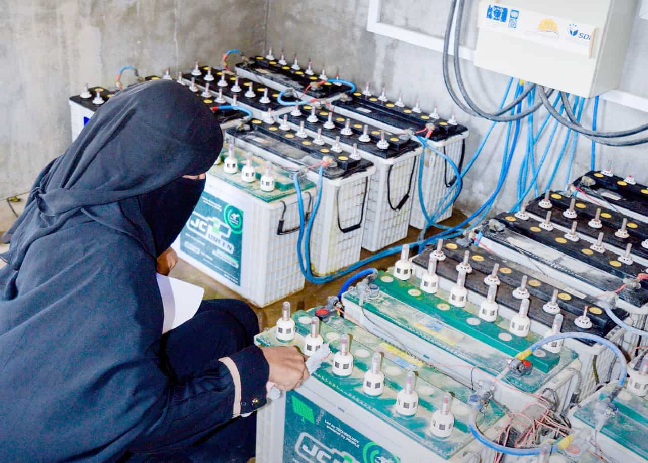 A woman connecting cables to batteries