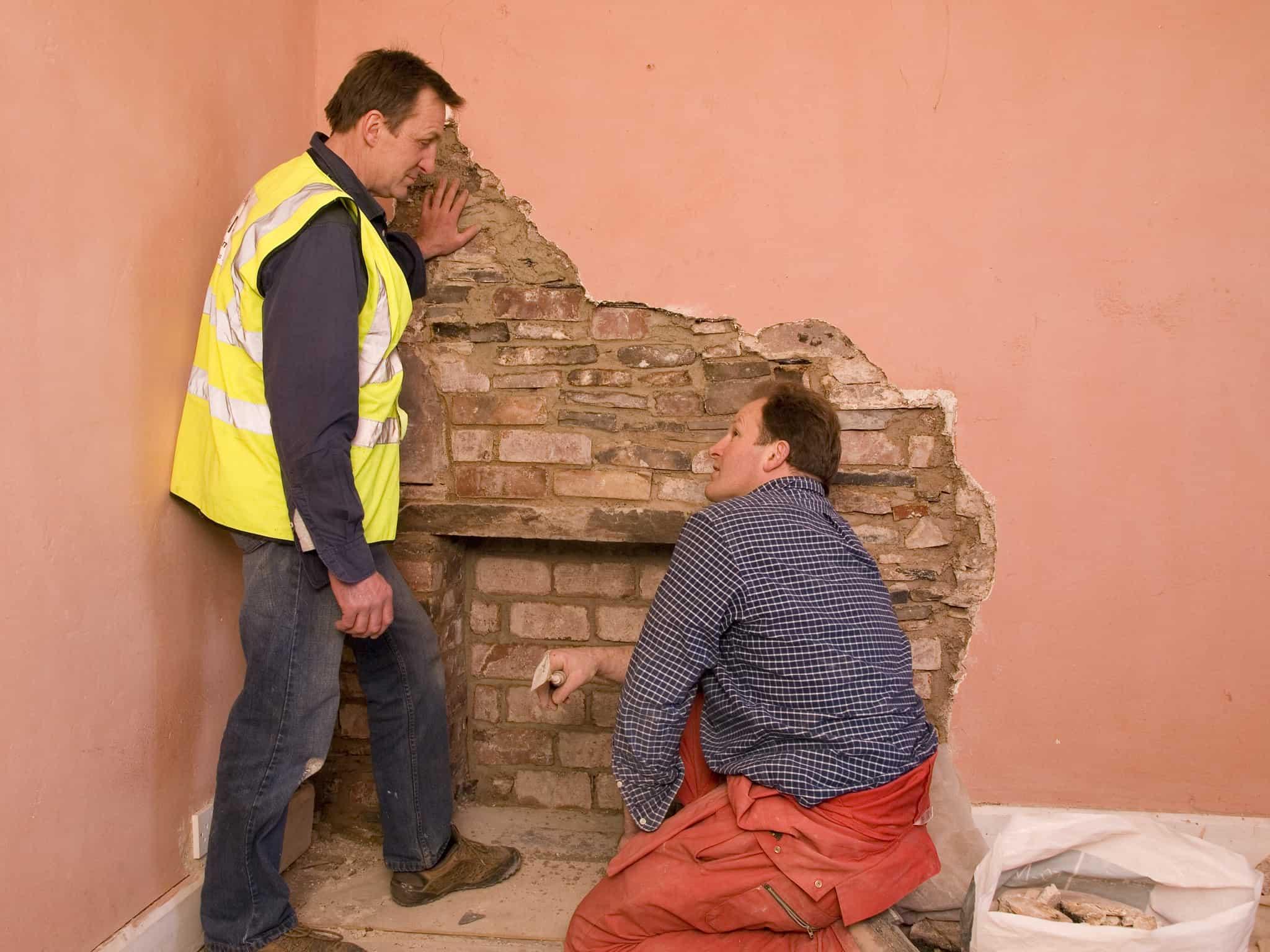 Two workmen look at exposed brickwork