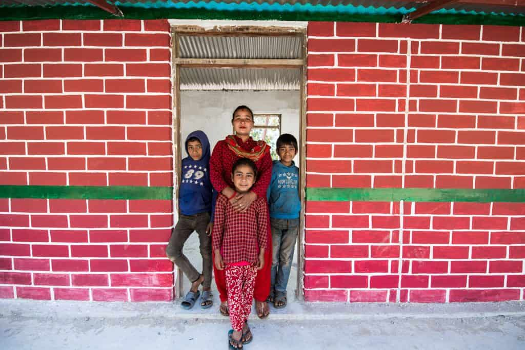 A family stand in a doorway