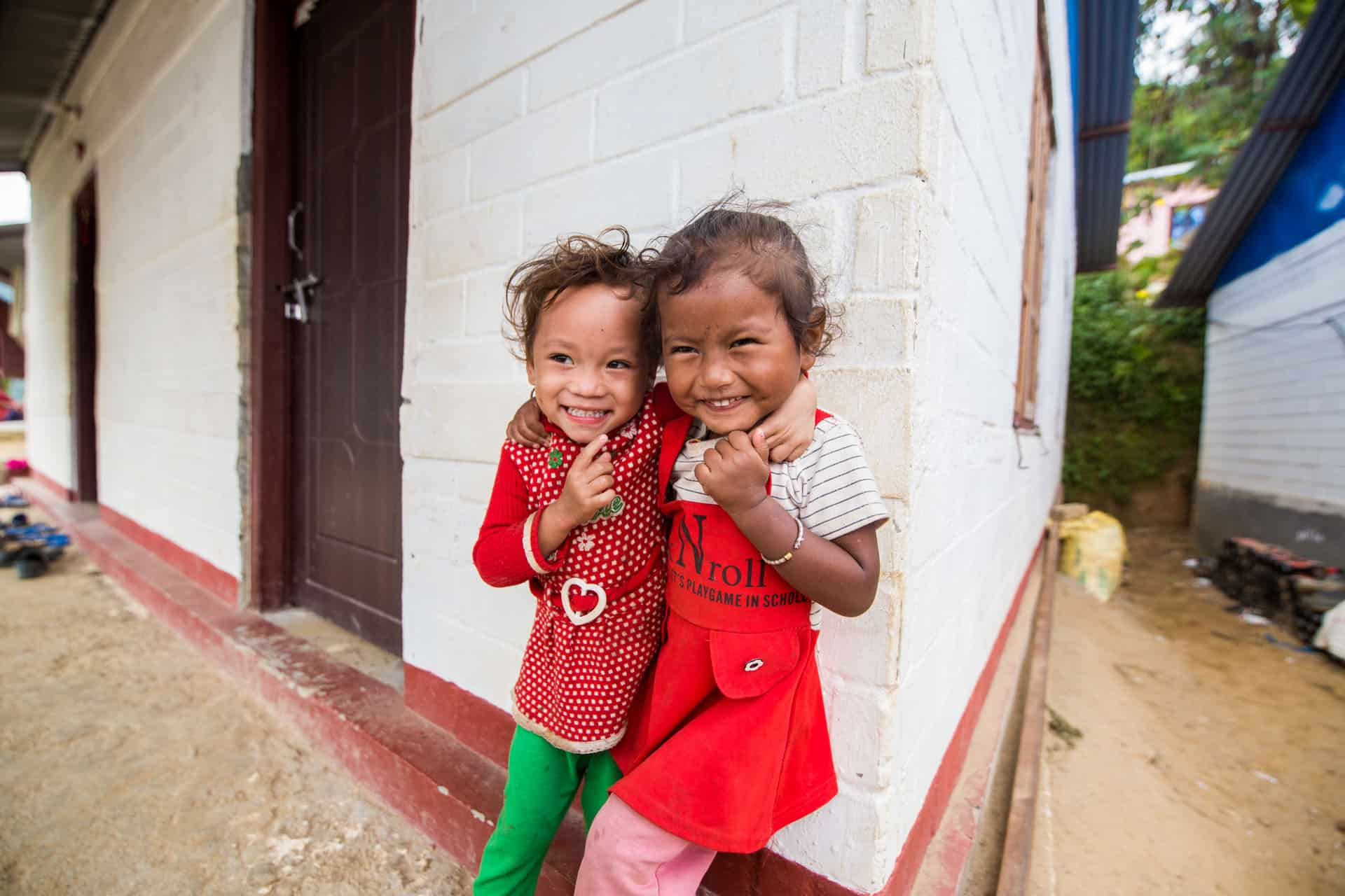 Two children smiling in front of a house