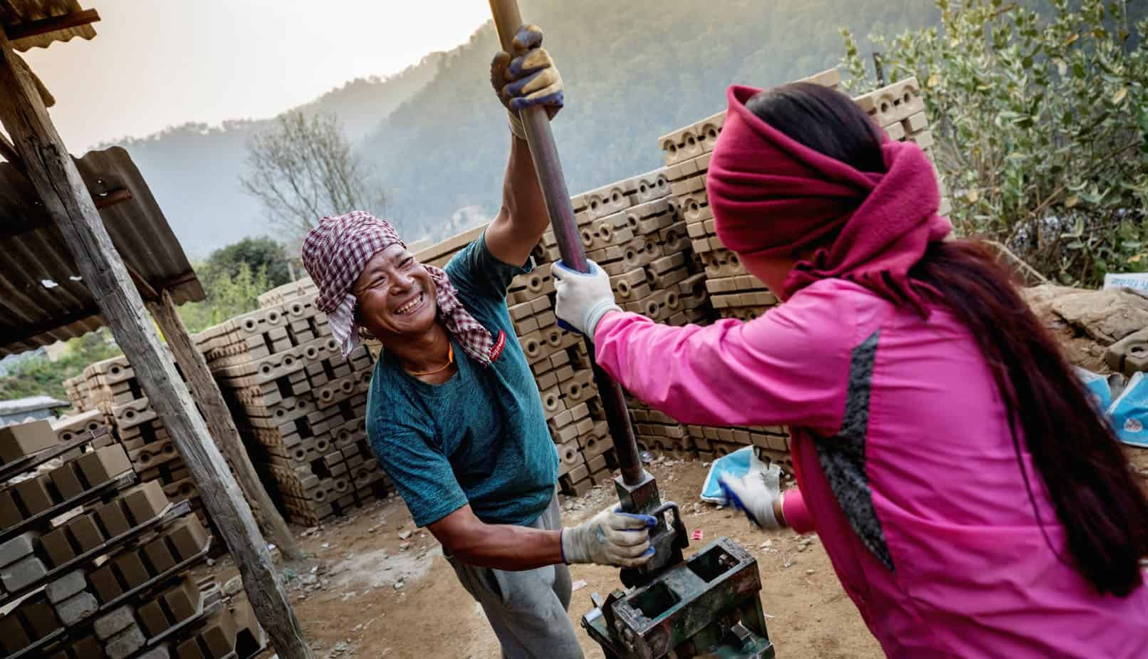A man and woman work machinery by a pile of bricks