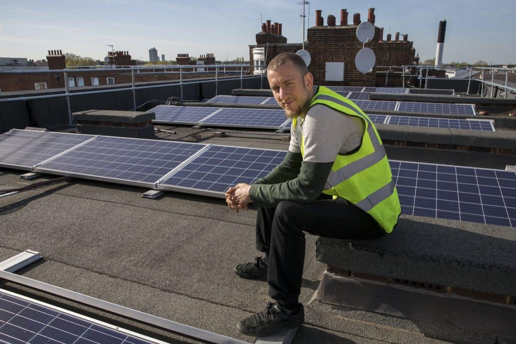 Man on rooftop next to solar panels