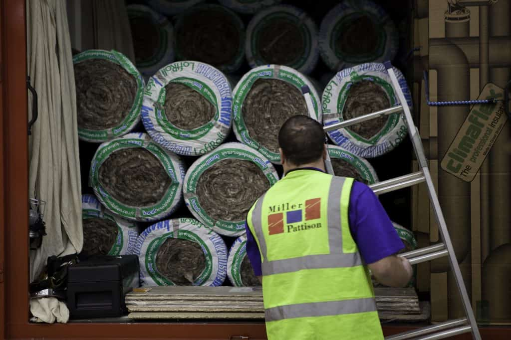 A man unloading insulating material