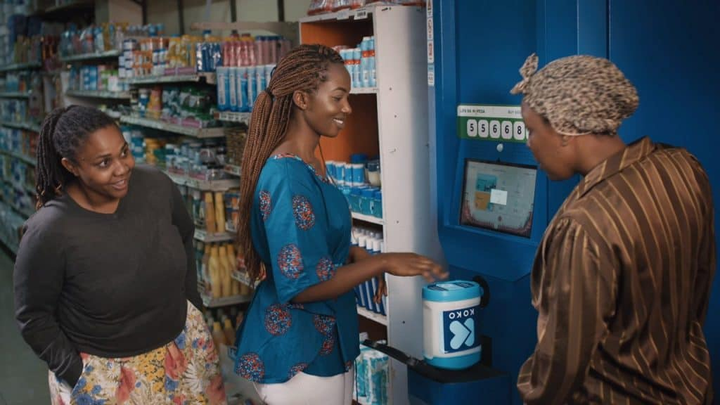 A woman filling a container at an ATM