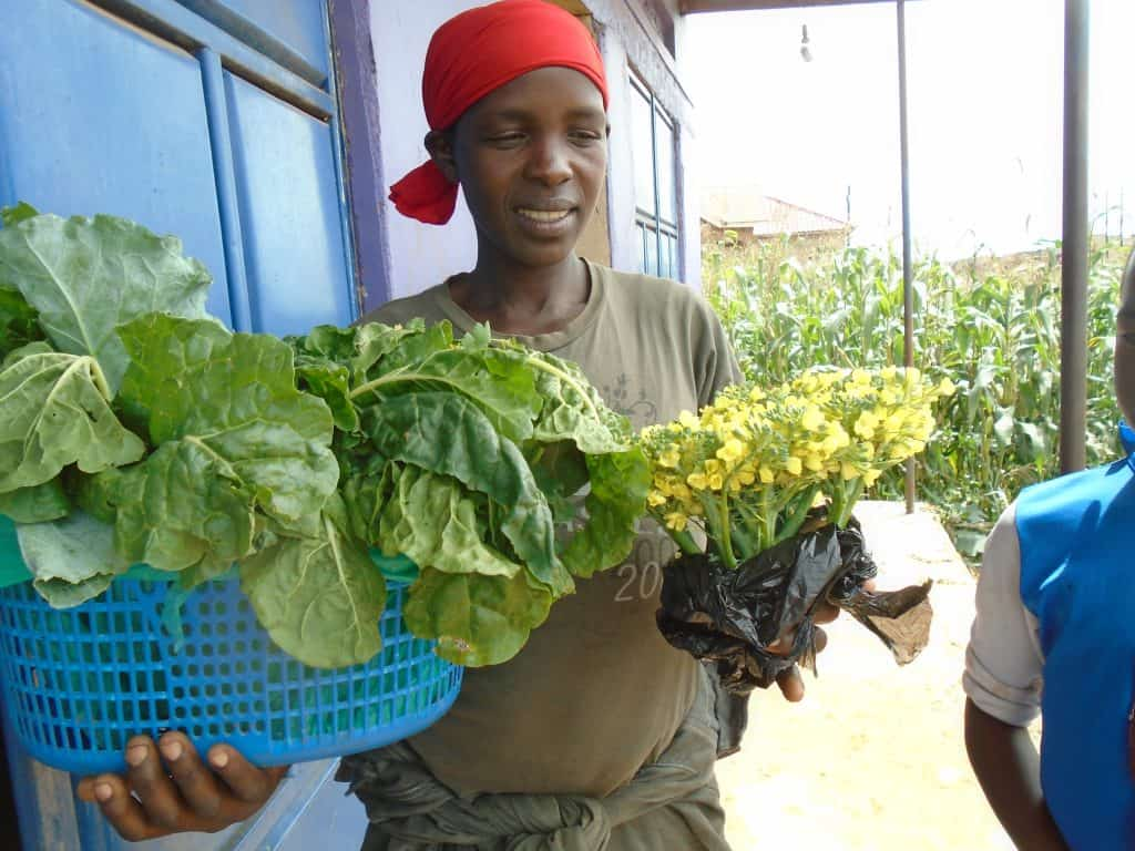 A woman holding some fresh vegetables