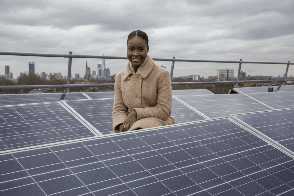 A woman kneeling by some solar panels