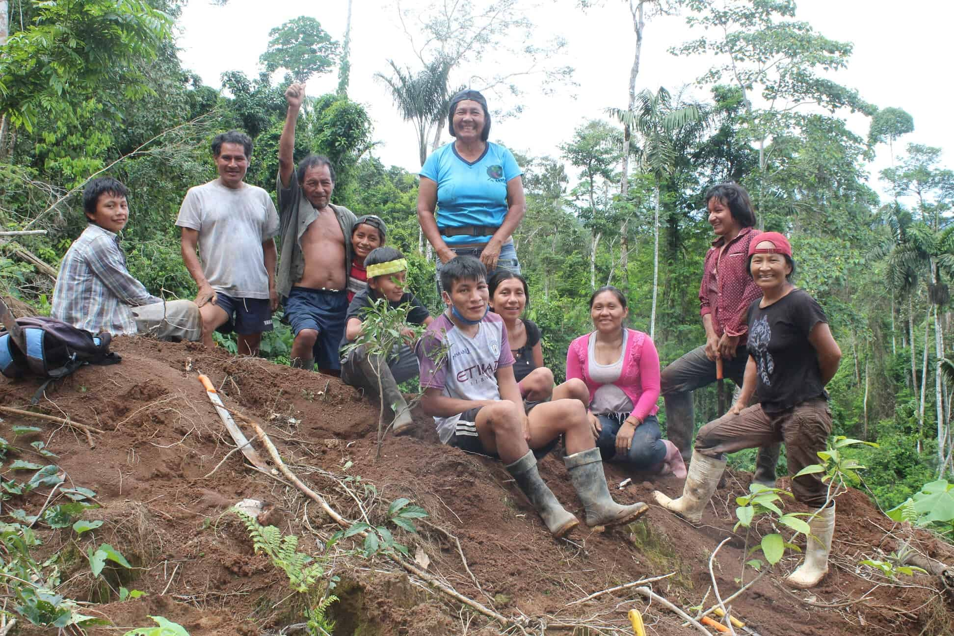 A group of Indigenous women and their families sit together on a small hill in the rainforest.