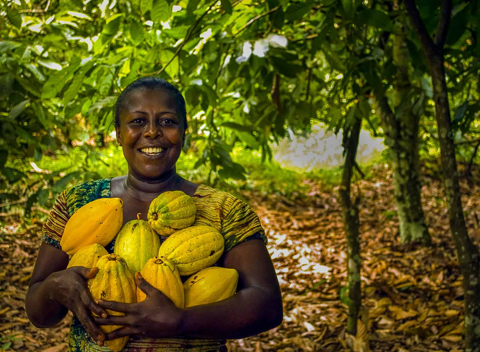 A woman stands smiling and holding a pile of bright yellow fruit surrounded by trees in the Amazon rainforest.