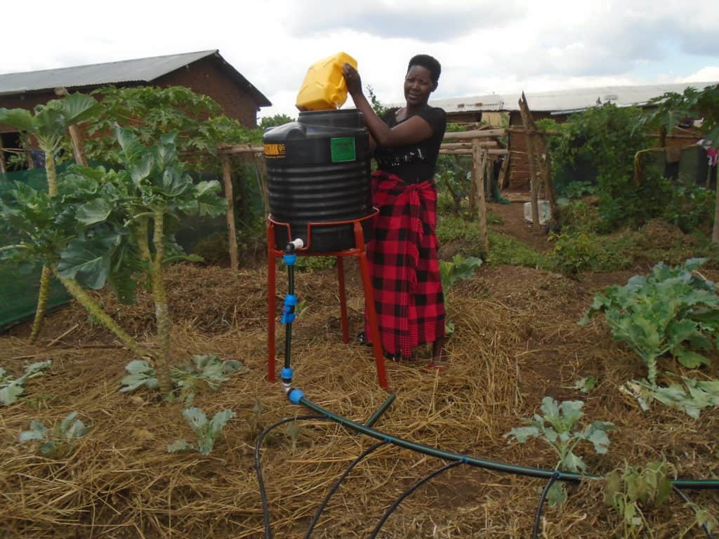 A female farmer fills her mobile drip-irrigation kit with a yellow bucket.