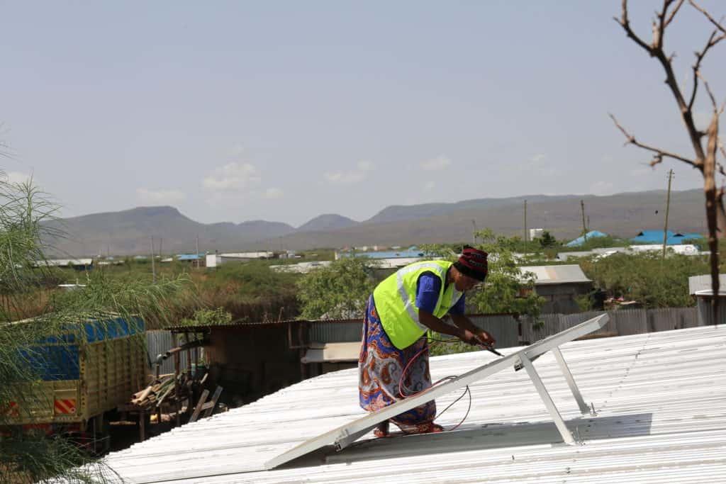 A female solar panel installer checks a solar panel on a hotel roof.