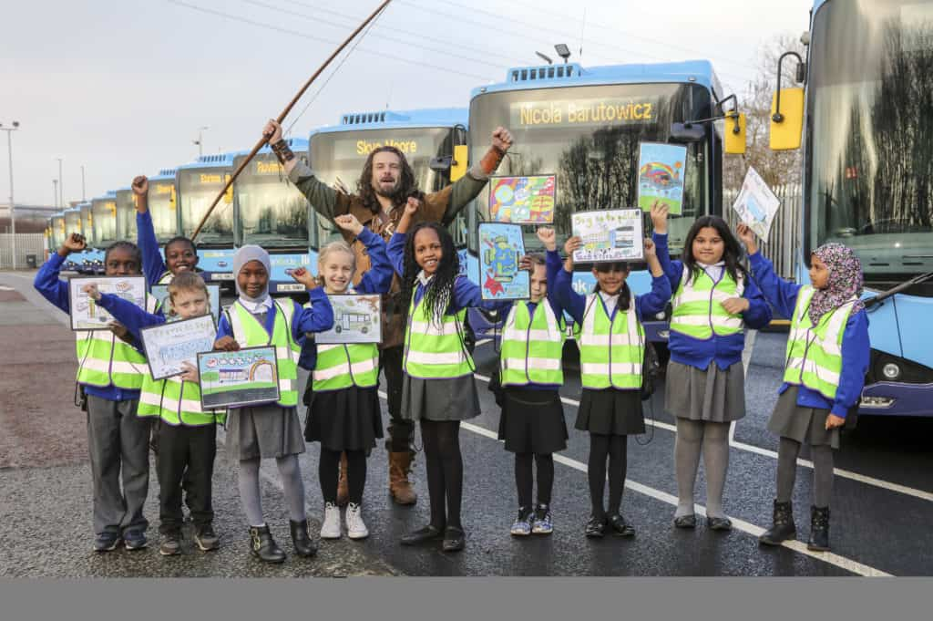 A group of children in hi-vis jackets holding drawings stand in front of new electric buses