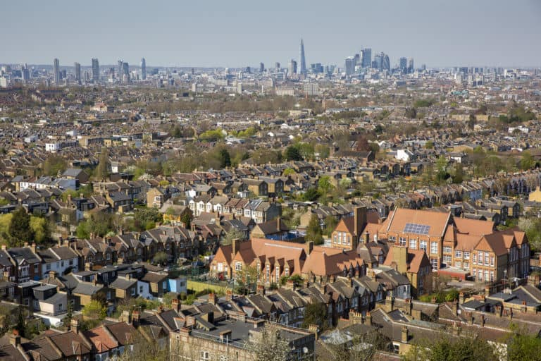 A landscape shot of houses in London, with the city's skyline in the background